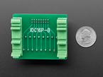 Bottom of PCB showing mounting hardware, next to quarter