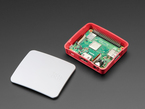 Angled shot of Raspberry Pi 3 A+ in an open red plastic case. A white case lid lies adjacent.