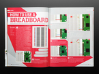 Opened book page to how to use a breadboard. Includes illustrations of a pi computer and breadboard.