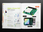 Opened book page to make a sense HAT mp3 player. Photographs of a Pi computer with sense HAT LEDs lighting up rainbow colors.