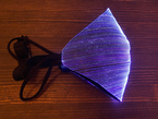 A folded black face mask with purple optic fibers folded on its side on a wooden desktop.