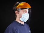 Face shield shown being worn by a model with a face mask