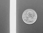 Close up of lit silicone bead LED strip next to quarter