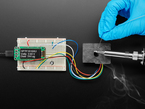 Person soldering next to sensor, which detects the fumes and shows air quality on OLED