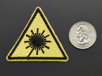 Triangle shaped yellow embroidered badge with laser symbol next to quarter for scale