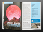 Open magazine spread featuring storm globe. Forget boring snow globes – build a swirling tempest for your desk using magnetic stirring and LED lightning. Image of a stormy, red cube amidst a mountain range.