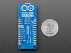 Bottom detail of Arduino showing silkscreen next to quarter
