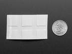 Cut paper with squares, next to quarter