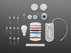 Kit contents with thread, sewing tools, batteries, and many LEDs