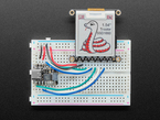 """Top view of a 1.54"""" tri-color eInk display assembled on a breadboard with jumper wires and a QT Py. Friendly snake in white-and-red, Blinka, on the display."""