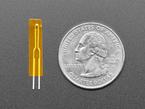 Top-down shot of mini thermistor sensor next to US quarter.