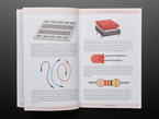 Book opened showing illustrations of a breadboard, jumper wires, an LED, and a resistor.