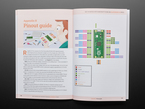 Book opened to Appendix B, Pinout guide. Pages contain illustration of a kid looking at a labeled diagram of the Raspberry Pi Pico.