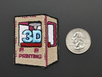 Embroidered badge of a 3D printer, next to quarter