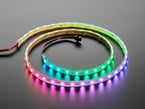 Angled shot of loosely coiled LED strip emitting pink-purple and blue-green lights.