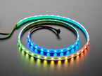 Angled shot of loosely coiled LED strip emitting green, blue, yellow, and orange lights.