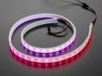 Angled shot of loosely coiled LED strip flashing pink and purple LEDs.