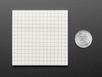 Gridded Sticky Notepad measured next to a US quarter