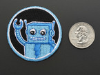 Circular embroidered badge with friendly blue robot waving on black background with blue trim, next to quarter for scale.