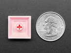 Bottom of pink plastic keycap next to US quarter.