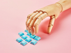 Close-up of a wooden artist's hand articulated over cyan blue keycaps against a pink background.
