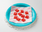 A picnic plate the color of robin egg's blue prepared with a lace doily. A pink and white striped napkin lies across the plate topped with red translucent keycaps, resembling fruit candy.