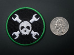 Circular embroidered badge with white skull over two crossed wrenches on black background with green trim. Next to quarter for scale.
