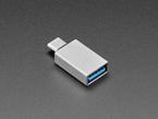 Angled shot of gray rectangular USA A socket to USB C plug adapter.