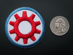 Circular embroidered badge with red gear on white background and blue trim. Next to quarter for scale.