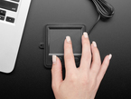 Top view of a hand using the trackpad and tactile buttons.