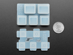 Bottom of Ctrl keycap mold pieces next to US quarter for scale.