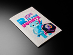 """A holographic sticker with friendly snake wearing a space-helmet. Text says """"Circuit Python Space Explorers"""" placed a book"""