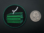 Circular embroidered badge with green dumpster and a white stick figure mid-dive, on black background with green trim. Shown next to a quarter for scale.