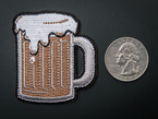 Closer shot of brewing badge next to a quarter for scale.