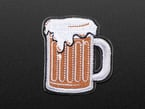Embroidered badge in the shape of a glass handled mug. Mug is filled with brown root beer and topped with white foam, badge is edged in black.