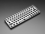 Angled shot of Silver Anodized Metal 60% / GH60 Keyboard Shell Plate assembled in a black keyboard enclosure.