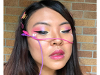 Picture of an Asian woman with makeup and wearing tropical colored alligator clips as hair accessories.