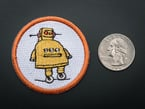 Circular embroidered badge with yellow Instructables robot on white background with orange trim. Shown next to a quarter for scale.