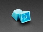 Two cyan keycaps stacked against eachother.