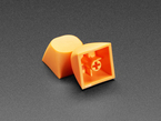 Two orange MA keycaps stacked against eachother.