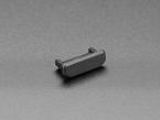 Angled shot of single black silicone mini HDMI dust cover.