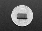 black silicone mini HDMI dust cover atop a US quarter for scale.