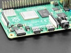 Close-up of a Raspberry Pi 4 with two black silicone dust covers protecting the micro HDMI ports.