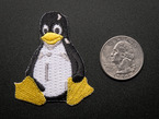 Embroidered badge in the shape of the sitting penguin Linux logo. In black and white, with yellow beak and feet. Shown next to a quarter for scale.