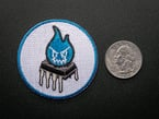 Circular embroidered badge with an evil blue flame over an OpAmp on white background with blue trim. Shown next to a quarter for scale.