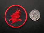 Circular embroidered badge with red CadSoft eagle logo on black background with red trim. Shown next to a quarter for scale.