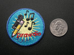 Circular embroidered badge with drawdio machine attached to a pencil, musical notes over a yellow light burst, on a blue background, with the word DRAWDIO in red. Shown next to a quarter for scale.