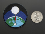 Circular badge with white high altitude balloon over a green and blue earth on a black background, with black trim. Shown next to a quarter for scale.