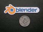 Embroidered badge in the shape of blender logo, with orange spinning wheel and the word BLENDER in blue on a white background. Shown next to a quarter for scale.