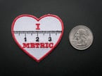 Heart shaped embroidered badge with the numbers 1, 2, 3 and the markings of a ruler in black over a white background. The words I and METRIC in red above and below the ruler. The badge is trimmed in red and shown next to a quarter for scale.